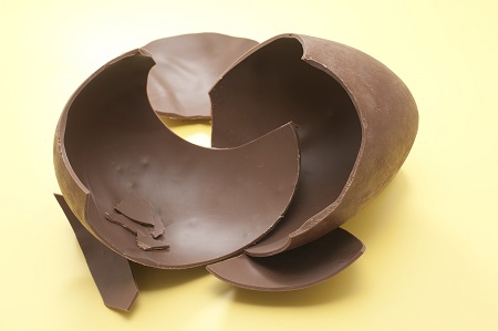 Pieces of a chocolate Easter Egg photographed over yellow.